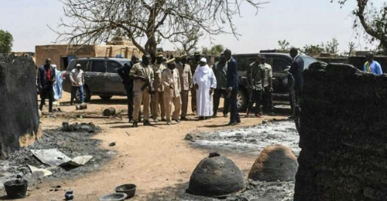 Conflict: President Ibrahim Boubacar Keita visits the village of Ogassogou in central Mali after 130 Fulani villagers were killed by Dogon hunters.  By Handout (MALIAN PRESIDENCY/AFP)