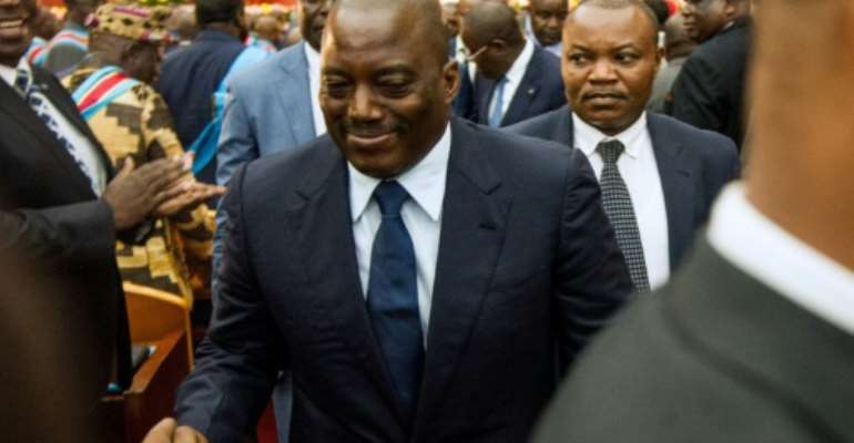 Congolese President Joseph Kabila (C) shakes hands during a special joint session of parliament on November 15, 2016 in Kinshasa.  By JUNIOR D.KANNAH (AFP/File)