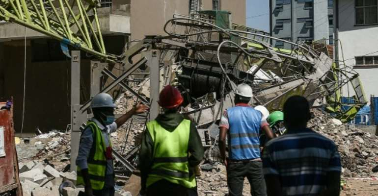 Contractors stand next to the collapsed crane in Kenya's capital Nairobi, on August 26, 2021..  By Simon MAINA (AFP)