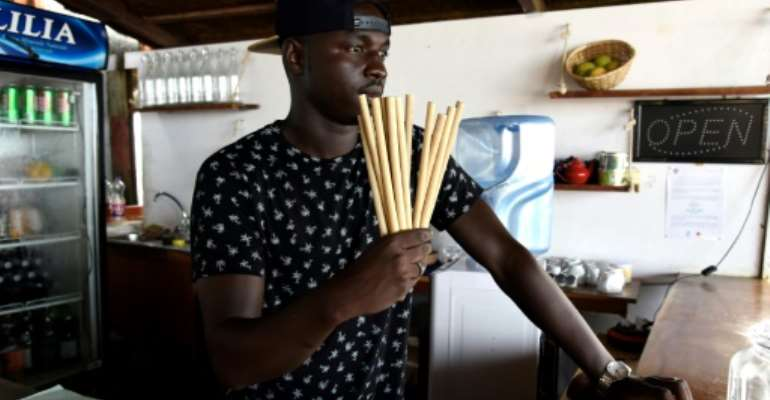 Copacabana restaurant owner Babacar Thiaw holds bamboo straws, replacing plastic straws -- a major and lasting source of marine pollution.  By SEYLLOU (AFP)