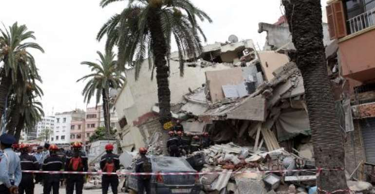 Moroccan rescuers inspect the rubble of a residential building that collapsed on July 11, 2014 in the city of Casablanca.  By  (AFP/File)