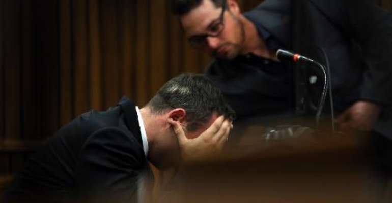 South African Paralympic track star Oscar Pistorius, flanked by his brother Carl (R), attends his trial in Court in Pretoria on April 7, 2014.  By Themba Hadebe (Pool/AFP)