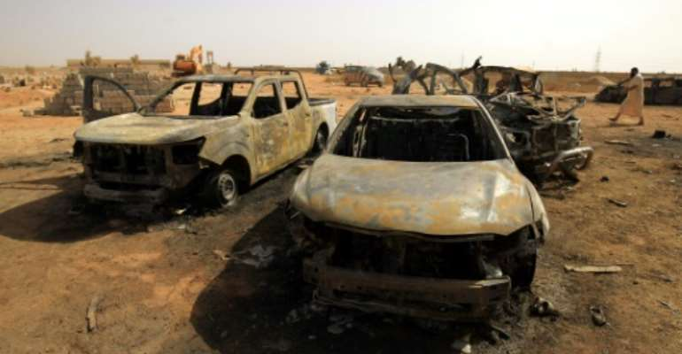 Damaged cars at the site of a bomb attack that targeted servicemen during the funeral of an ex-army commander in the Libyan city of Benghazi.  By Abdullah DOMA (AFP)