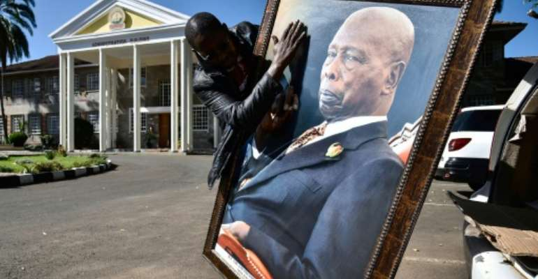 Daniel arap Moi, who towered over Kenya between 1978 and 2002, lay in state for three days in parliament, with tens of thousands of people filing past to pay their respects.  By SULEIMAN MBATIAH (AFP/File)