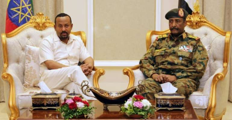 Days after a deadly crackdown on a protest camp in Khartoum, Ethiopia's Prime Minister Abiy Ahmed (L, pictured June 7, 2019) met with Sudan's ruling military council General Abdel Fattah al-Burhan (R) to try to mediate between the two sides.  By - (AFP/File)