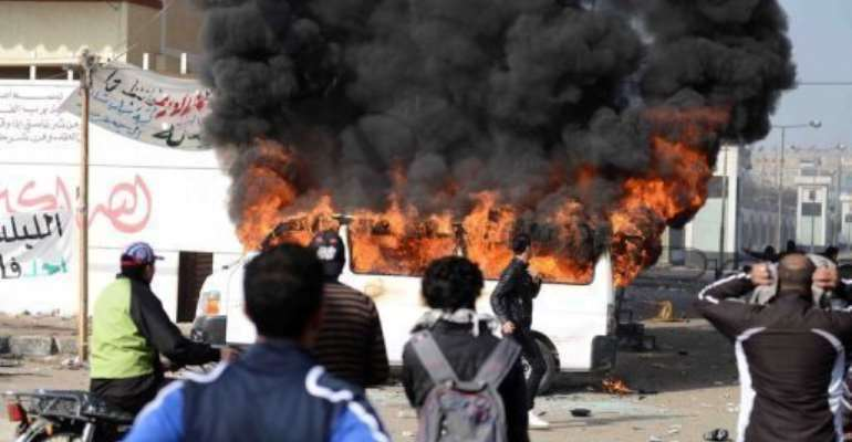 Smoke billows from a minibus belonging to a satellite channel outside the Port Said prison on January 26, 2013.  By  (AFP)