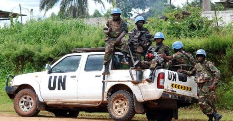 Blue helmet members of MONUSCO sit on the back of a UN pick-up truck on October 23, 2014 in Beni.  By Alain Wandimoyi (AFP/File)