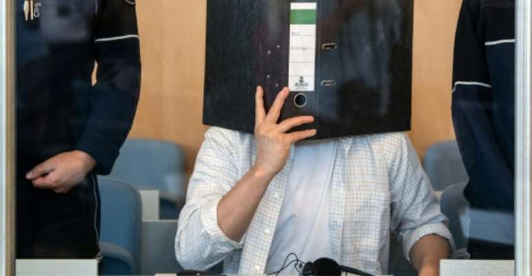 Defendant Sief Allah H. holds a folder in front of his face at the start of his trial on June 7, 2019 at a court in Duesseldorf, western Germany.  By Federico Gambarini (dpa/AFP/File)