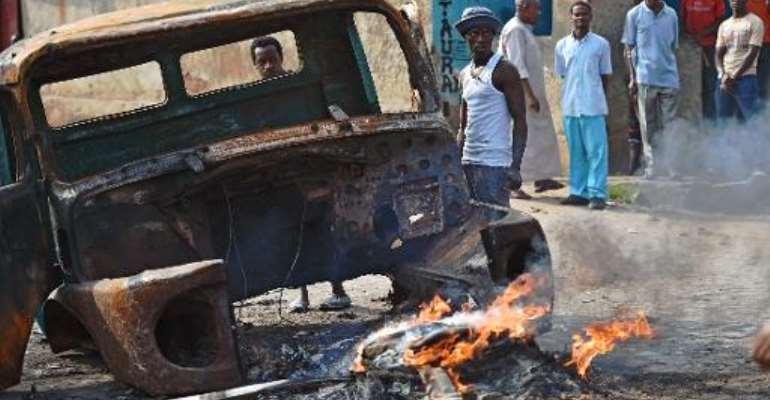 Protestors opposed to Burundian President Pierre Nkurunziza's third term stand beside a burning vehicle during a demonstration in the Buyenzi neighborhood of Bujumbura on May 26, 2015.  By Carl De Souza (AFP)