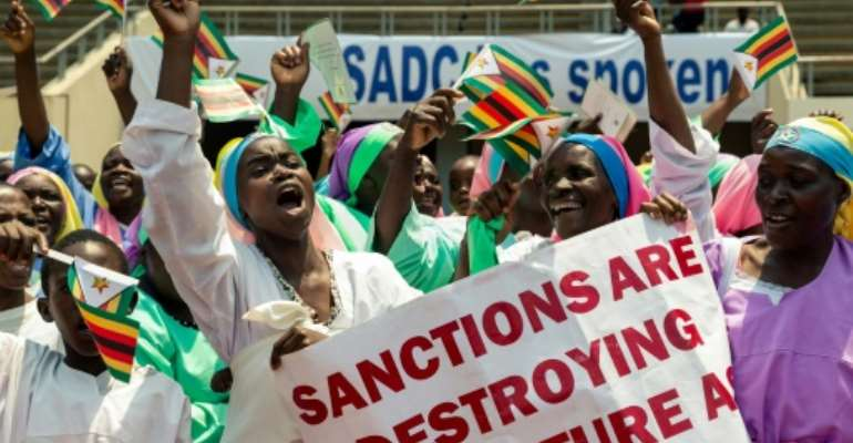 Demonstrators chant slogans and wave Zimbabwe's national flag during a rally to denounce US and EU economic sanctions.  By Jekesai NJIKIZANA (AFP)