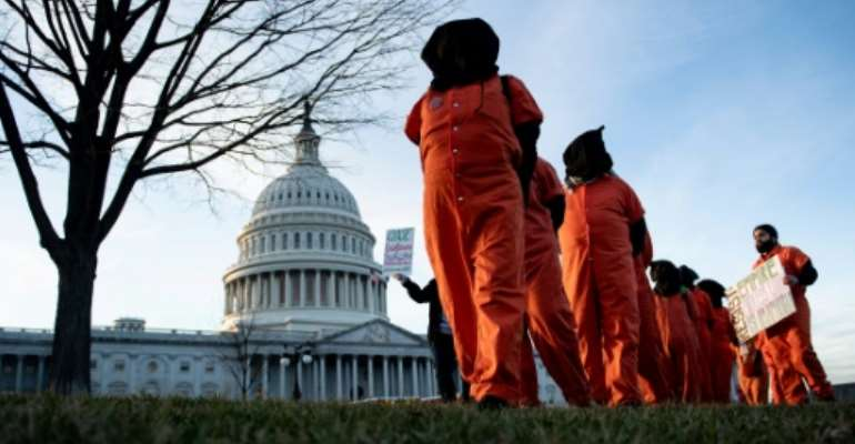 Demonstrators dressed in Guantanamo Bay prisoner uniforms march past Capitol Hill in Washington, DC, on January 9, 2020.  By Brendan Smialowski (AFP/File)