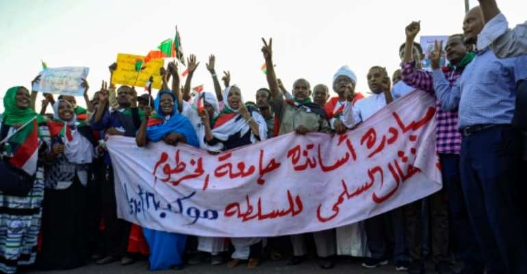 Demonstrators outside of Sudan's army headquarters call for a quick turn to civilian rule.  By MOHAMMED HEMMEAIDA (AFP)