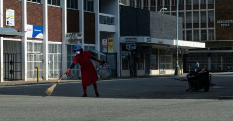 Deserted: A street cleaner in Harare on day one of Zimbabwe's three-week lockdown.  By Jekesai NJIKIZANA (AFP)