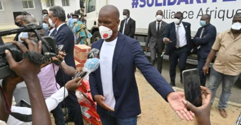Didier Drogba speaks to media as he helps distribution of food and sanitary  products in Abidjan.  By ISSOUF SANOGO (AFP)