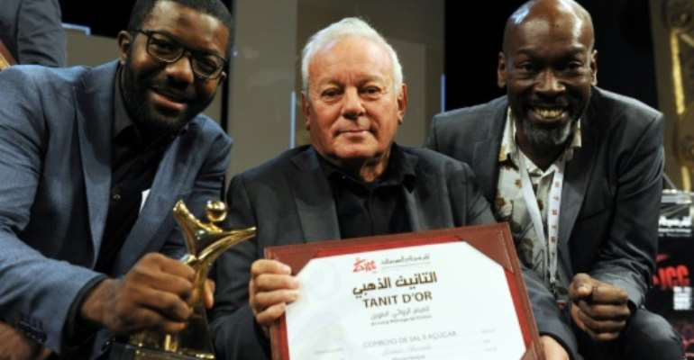 Director Licinio Azevedo (C), flanked by actors Matamba Joaquim (L) and Thiago Justino, poses after receiving the Tanit d'Or award for his film