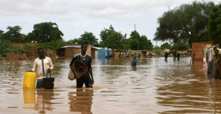Dozens of residents in the capital Niamey fled their homes earlier on Thursday, wading or swimming through flooded streets.  By BOUREIMA HAMA (AFP)
