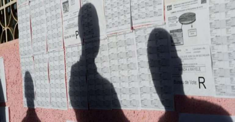 A Congolese man checks his name against the list of registered voters.  By Phil Moore (AFP)