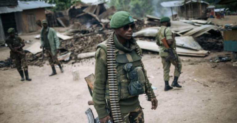 DR Congo's armed forces are struggling to cope with a surge of attacks by the ADF militia. Here, troops patrol the village of Manzalaho after a raid in February last year.  By Alexis Huguet (AFP/File)