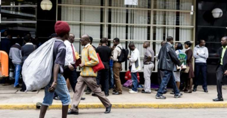 Due to Zimbabwe's crippling cash shortage, banks limit withdrawals meaning that long queues of people waiting outside are a common sight.  By ZINYANGE AUNTONY (AFP/File)