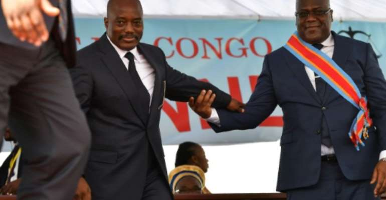During his inauguration DR Congo's new president, Felix Tshisekedi, (R) walks off the podium with outgoing leader Joseph Kabila in Kinshasa in January 2019.  By TONY KARUMBA (AFP/File)