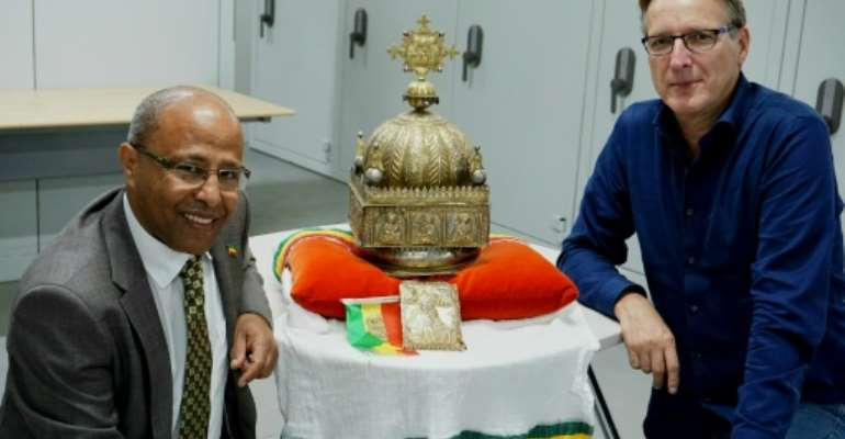 Dutch-Ethiopian Sirak Asfaw, left, and art detective Arthur Brand pose with the coveted crown at a high-security facility in the Netherlands in September last year.  By Jan HENNOP (AFP)