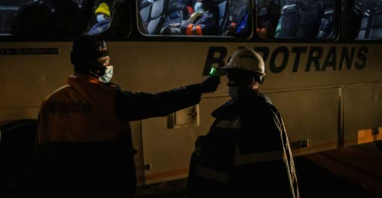 Each shift at the Sibanye-Stillwater platinum mine in South Africa now begins with a temperature check, part of screening measures to stem the spread of the novel coronavirus.  By Michele Spatari (AFP)