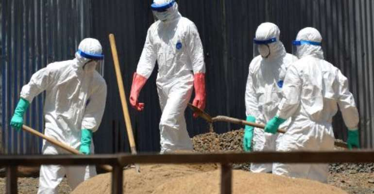 Workers from the Liberian Red Cross at ELWA 2 Ebola management center in Monrovia on October 23, 2014 shovel sand which will be used to absorb fluids emitted from the bodies of Ebola victims.  By Zoom Dosso (AFP)