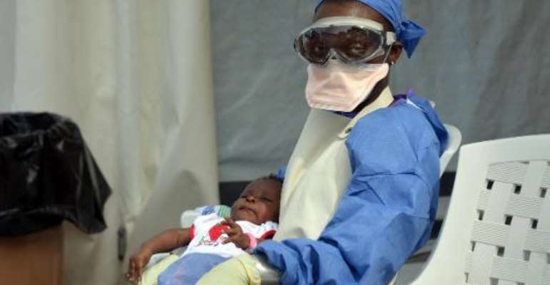 A Liberian health worker holds a baby infected with the Ebola virus at the NGO Medecins Sans Frontieres (Doctors Without Borders) Ebola treatment center in Monrovia on October 18, 2014.  By Zoom Dosso (AFP/File)