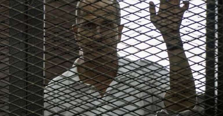 Australian Al-Jazeera journalist Peter Greste listens to the verdict in Cairo on June 23, 2014 inside the defendants cage during his trial for allegedly supporting the Muslim Brotherhood.  By Khaled Desouki (AFP/File)