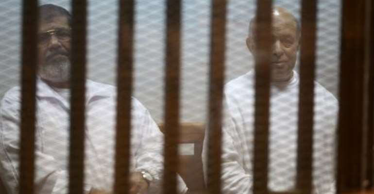 Egypt's deposed president Mohamed Morsi (left) and his former chief of staff Refaa al-Tahtawi sit inside the defendants' cage during their 2014 trial in Cairo.  By Ahmed Ramadan (AFP/File)