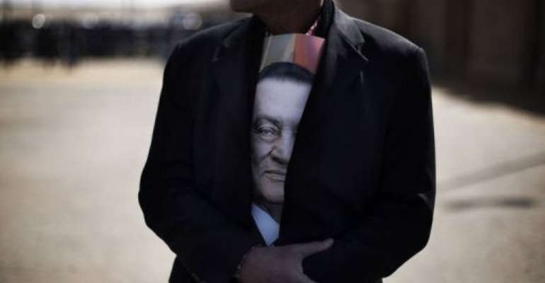 A supporter of ousted Egyptian president Hosni Mubarak outside the court in Cairo.  By Marco Longari (AFP)