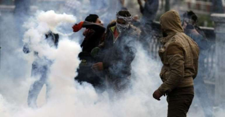 An Egyptian protester throws a tear gas canister back towards riot police during clashes in Cairo on January 29, 2013.  By Mohammed Abed (AFP)