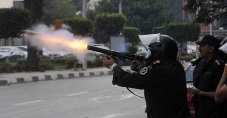 An Egyptian riot policeman fires a tear gas cannister towards demonstrating students of al-Azhar University who support the Muslim Brotherhood during clashes outside their campus in Cairo on December 9, 2013.  By Tarek Wajeh (AFP)