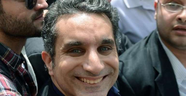 Egyptian satirist and television host Bassem Youssef is surrounded by his supporters upon his arrival at the public prosecutor's office in the high court in Cairo, on March 31, 2013.  By Khaled Desouki (AFP/File)