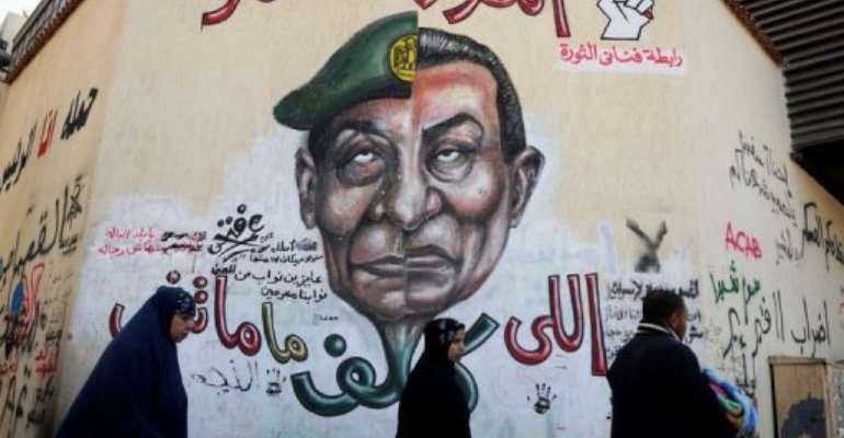 Egyptians walk past graffiti with a slogan reading,