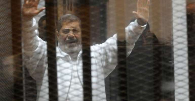 Egypt's deposed Islamist president Mohamed Morsi waves from inside the defendants' cage during his trial at the police academy in Cairo on January 8, 2015.  By  (AFP/File)