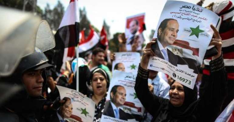 Egyptians hold portraits of President Abdel Fattah al-Sisi in front of the presidential palace of Ethadya in the capital Cairo on June 8, 2014.  By Mohamed el-Shahed (AFP/File)