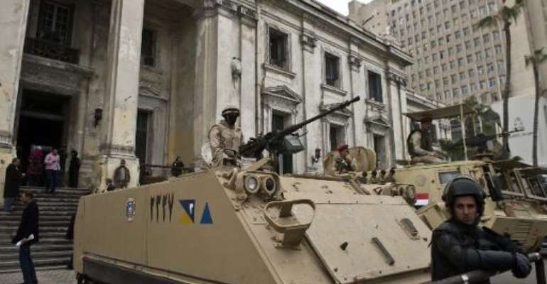Egyptian soldiers and police stand guard with armoured personnel carriers (APC) outside the criminal court in the Mediterranean city of Alexandria on March 3, 2014.  By Khaled Desouki (AFP/File)