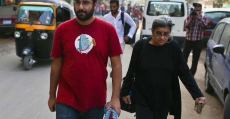 Egyptian activist Alaa Abdel Fattah (left), who along with his sister is back in detention, walks with his mother Leila after a 2014 court hearing in Cairo.  By Mohamed el-Shahed (AFP/File)