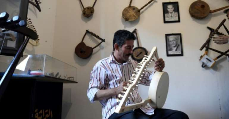 Egyptian craftsman Mohamed Ghaly adds the finishing touches on a semsemia that he made at the Canal 20 cultural museum in Port Said which he founded to pass on the musical heritage to a new generation.  By Khaled DESOUKI (AFP)