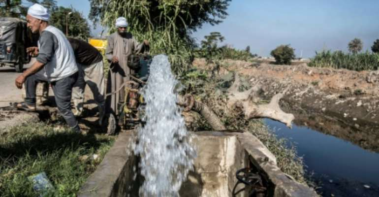 Egyptian farmers supply their farmland with water from a canal, fed by the Nile river, in a village outside of the capital Cairo.  By Khaled DESOUKI (AFP/File)