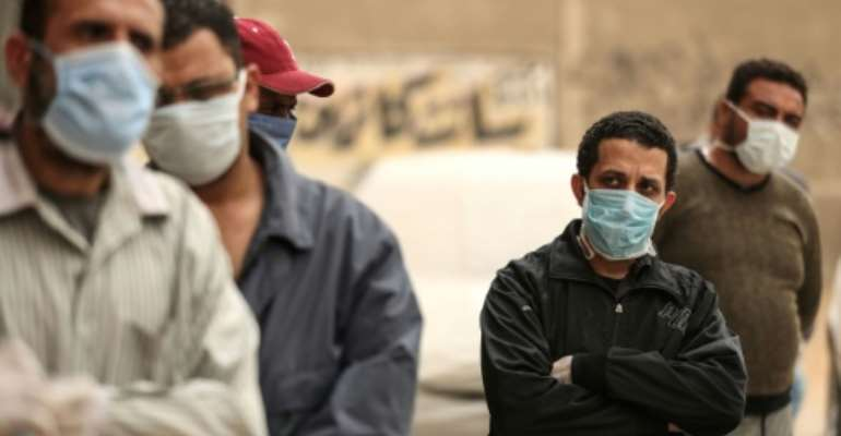 Egyptian men wait outside a food bank, after movement restrictions imposed to fight coronavirus crippled already precarious livelihoods.  By Mohamed el-Shahed (AFP)