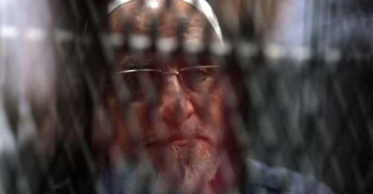 Egyptian Muslim Brotherhood Supreme Guide Mohamed Badie is seen behind bars during a hearing for him and other Brotherhood members on charges of espionage, as the country's crackdown on the Islamist group continues.  By Khaled KAMEL (AFP/File)