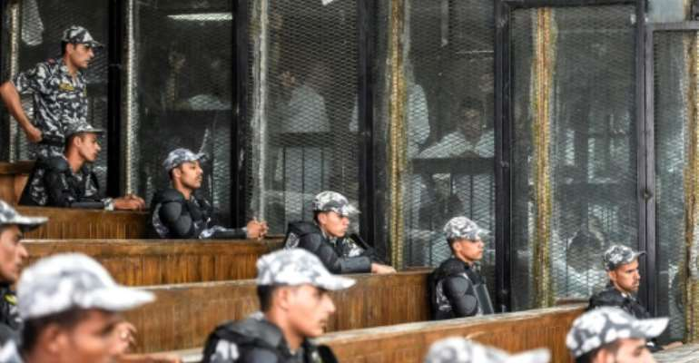 Egyptian security peronnel line the public gallery as Muslim Brotherhood members appear in the caged dock at a trial hearing in July 2018.  By Khaled DESOUKI (AFP/File)