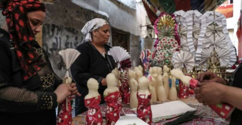 Egyptian women decorate traditional sugar statuettes in the capital Cairo for Al Mawlid Al Nabawi celebrations.  By Mohamed el-Shahed, Mohamed el-Shahed (AFP)