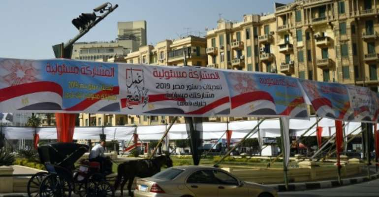 Egyptians pass under banners reading in Arabic