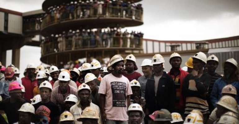 Miners of Harmony Gold's Doornkop mine gather to mourn their colleagues who died in a mining accident in Doornkop, southwest of Johannesburg, on February 6, 2014.  By Marco Longari (AFP)