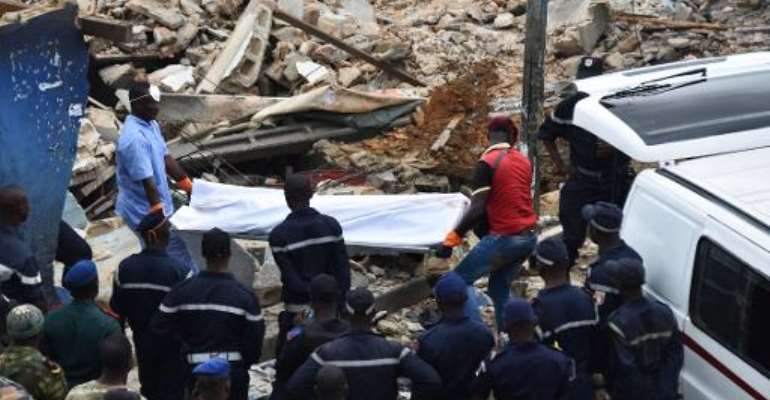 Rescuers carry the body of a man after a building collapsed during demolition work on November 5, 2014 in the Attecoube neighbourhood of Abidjan.  By Sia Kambou (AFP)