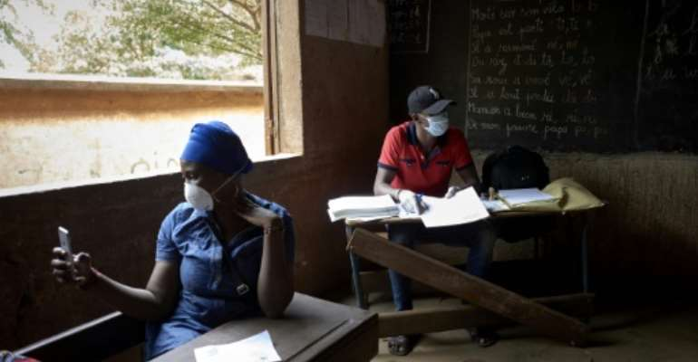 Electoral officials wore masks and gloves as a preventive measure against the spread of the coronavirus during Mali's parliamentary elections.  By MICHELE CATTANI (AFP)