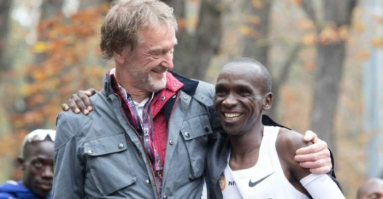 Eliud Kipchoge celebrates with Ineos owner Jim Ratcliffe after the Kenyan broke the two-hour marathon barrier in an event heavily sponsored by the petrochemicals company.  By ALEX HALADA (AFP/File)